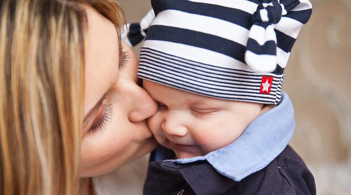 Baby mit Mütze bekommt einen Kuss von Mama. Die richtige Mützengröße für Ihr Baby hat Sie vorher durch Messen des Kopfumfangs und einen Blick in die Baby Mützengrößen Tabelle herausgefunden.
