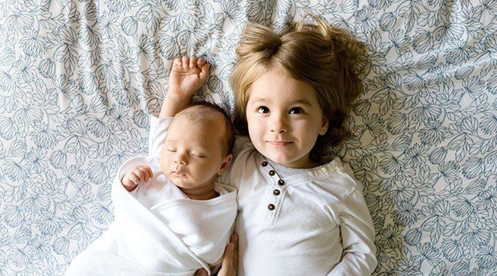 Der kleine Bruder liegt zufrieden im Arm der stolzen großen Schwester. Die richtige Kindergröße bei Kinderkleidung ist wichtig für das Wohlbefinden und den Entwicklungsprozess. Alle Kindergrößen für Kleidung, Mützen, Schuhe und mehr, findest du auf kindergroessen.info