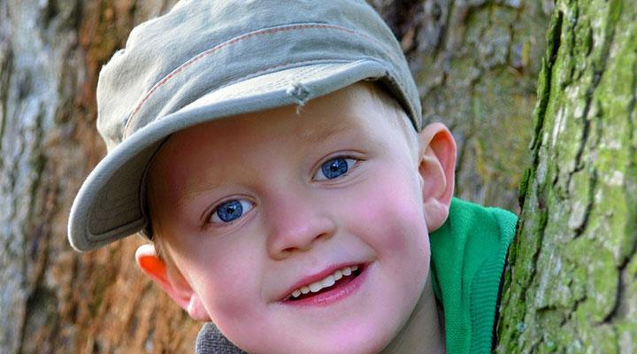 Mützengrößen Kinder – Junge mit Cappi guckt hinter Baum hervor