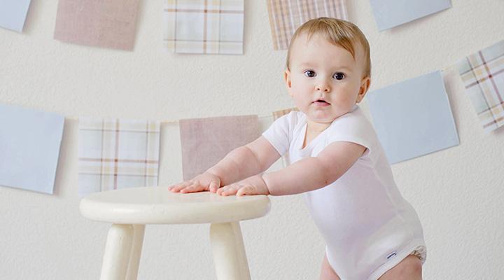 Baby steht an einem Hocker – Babygrößen auf einen Blick